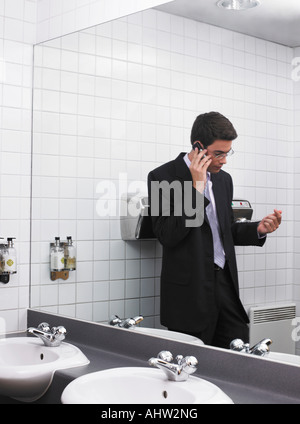 Man reflected in office washroom mirror using mobile phone - Stock Photo
