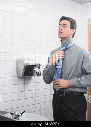 Man reflected in office washroom mirror doing up his tie - Stock Photo