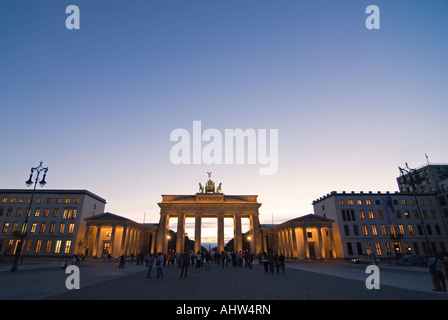 Horizontal wide angle of the Brandenburg Gate on Pariser Platz illuminated in the evening with lots of tourists. - Stock Photo