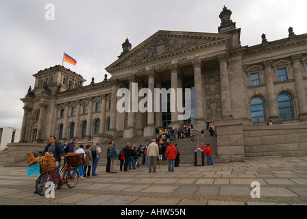 Horizontal wide angle of a local man selling bagels to tourists queueing outside the Reichstag in Platz de Republic. - Stock Photo