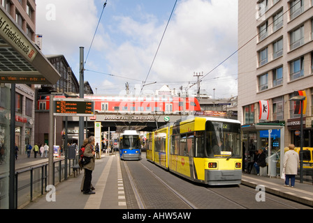 Horizontal wide angle cityscape of Friedrichstrasse with a train departing the station and two trams approaching - Stock Photo