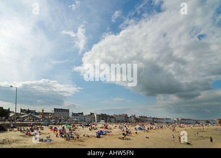 Horizontal wide angle of a typical English beach scene with lots of tourists on the sand at Weymouth Bay. - Stock Photo