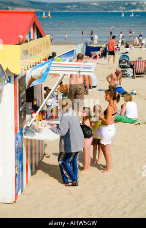 Vertical view of tourists queueing at a bright traditional fish and chip fastfood stand on the beach at Weymouth. - Stock Photo