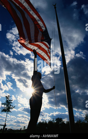 This is a Park Ranger raising the American flag on its flagpole He is silhouetted arm reaching up against a blue - Stock Photo
