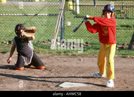 Little league action the batter hits the ball - Stock Photo