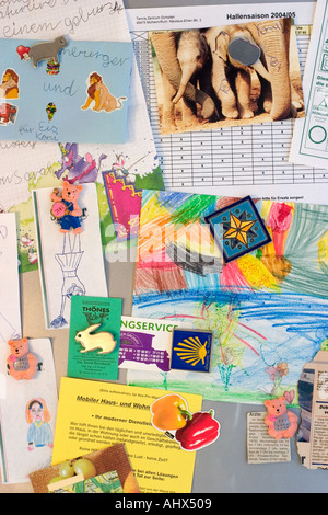 A refrigerator door with multiple magnets and art - Stock Photo