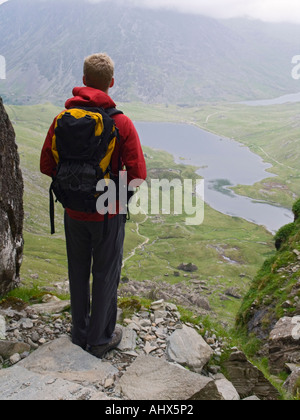 Young man standing alone looking down to Llyn Idwal in the cwm from Devil's Kitchen footpath in Snowdonia National - Stock Photo
