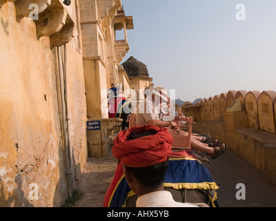 Amber Jaipur Tourists riding elephant taxis to Amber Fort from elephant seat looking over mahout's red turban - Stock Photo