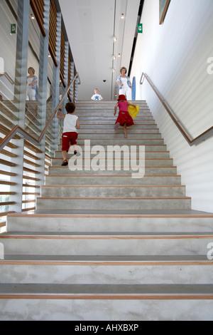 Children running up steps in interior of Gallery of Modern Art Brisbane Queensland QLD Australia - Stock Photo