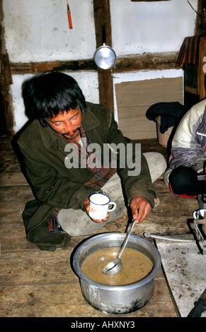 Bhutan Paro Bhutanese man pouring yak butter tea in kitchen - Stock Photo