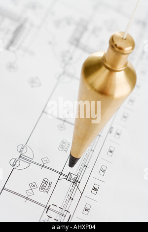 Plumb bob above blueprints - Stock Photo
