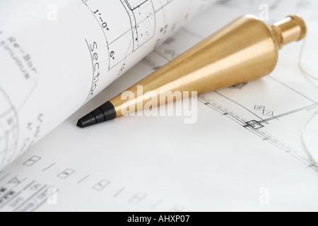Plumb bob with blueprints - Stock Photo