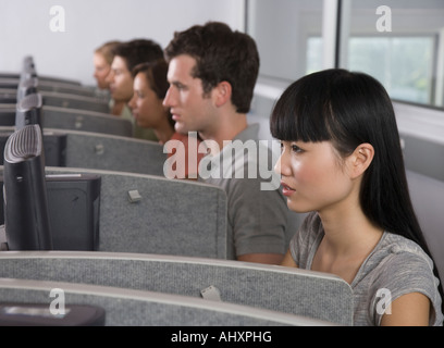 College students wearing headsets in computer lab - Stock Photo