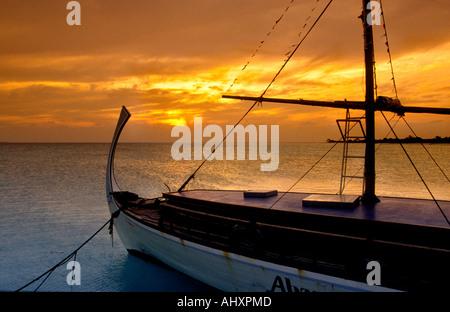 Maldives Kuredhu resort sun setting over dhoni - Stock Photo