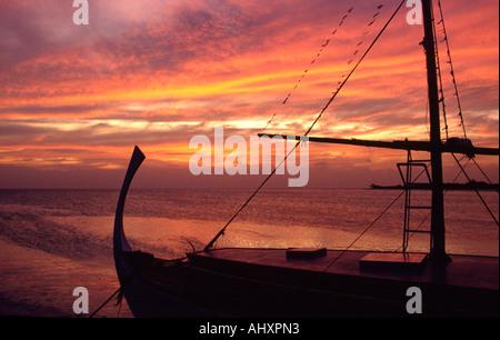 Maldives Kuredhu resort sunset over dhoni - Stock Photo