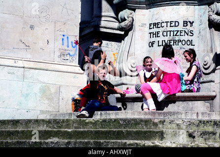 Children on Queen Victoria monument in Derby Square Liverpool - Stock Photo