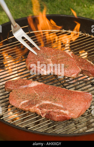 Steaks cooking on grill - Stock Photo