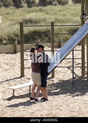 Couple dancing together in a children's playground beside the beach. - Stock Photo