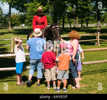 A group of people talking to a mountie at the RCMP (Royal Canadian Mounted Police) Musical Ride centre in Ottawa, - Stock Photo