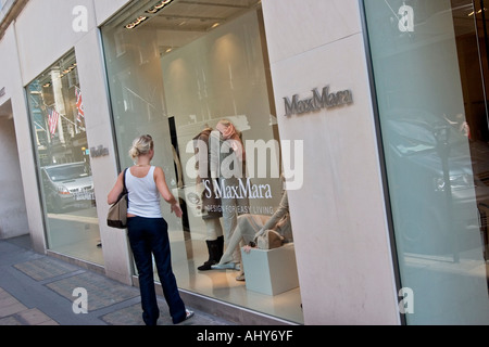 Young woman looks in Max Mara shop window on Bond Street - Stock Photo