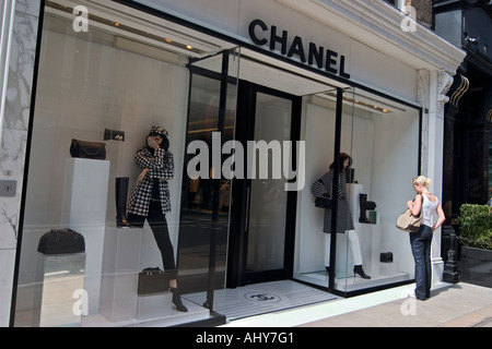 Young woman looks in Chanel shop window on Bond Street - Stock Photo