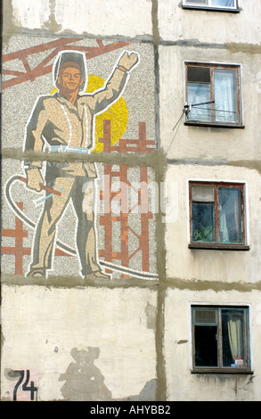 A Soviet era mosaic of a worker on the side of an apartment block in Yuzhno Sakhalinsk on Sakhalin 2004 - Stock Photo