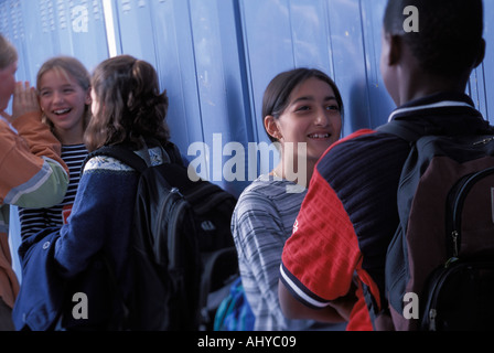 A group of multi racial students hanging out in a middle school hallway - Stock Photo