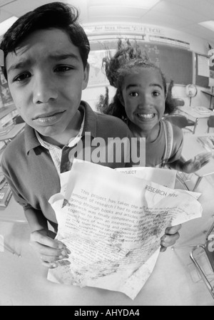Two Latino middle school students with messy homework papers Using the excuse 'the dog ate my homework' - Stock Photo