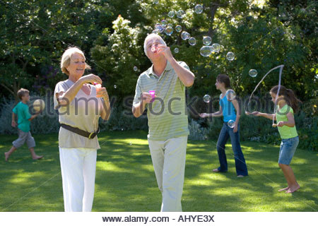 Children 8 13 playing with ball on garden lawn grandparents blowing soap bubbles into air with bubble wand in foreground - Stock Photo