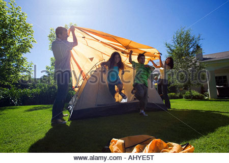 Family assembling dome tent in garden parents placing outer canvas over tent frame children running out of way backlit - Stock Photo
