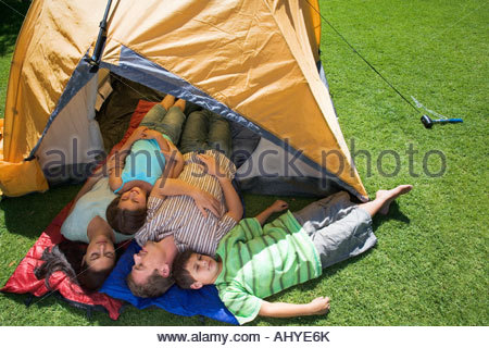 Family lying on sleeping bags in tent entrance on garden lawn eyes closed elevated view - Stock Photo