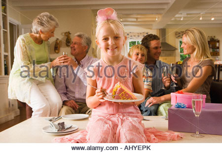 Three generation family sitting on sofa at home, girl sitting on coffee table with slice of birthday cake portrait - Stock Photo