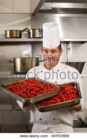 Male chef carrying two full trays of red chili peppers in commercial kitchen smiling portrait - Stock Photo