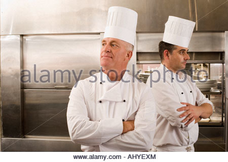 Two male chefs standing in commercial kitchen arms folded looking in opposite directions - Stock Photo