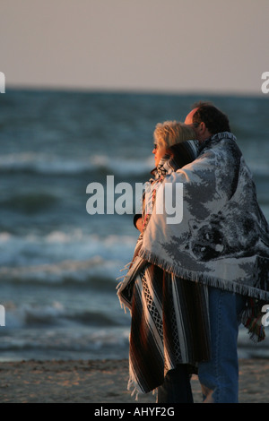 Couple standing on beach wrapped in blankets looking at the sun - Stock Photo