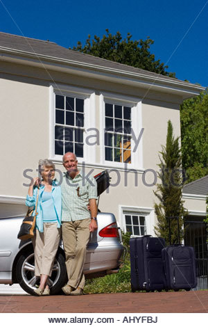 Senior couple standing beside parked convertible car on driveway, smiling, portrait, suitcases near open boot surface - Stock Photo