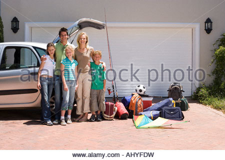 Family standing beside parked car with open boot near camping equipment on driveway smiling portrait - Stock Photo