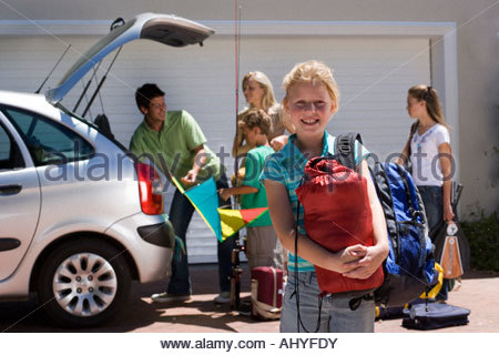 Family loading camping equipment into parked car boot on driveway, girl carrying rucksack and sleeping bag in foreground - Stock Photo