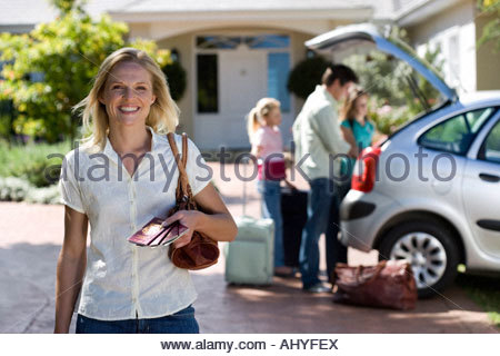Family loading parked car boot on driveway focus on mother standing with tickets in foreground smiling portrait - Stock Photo