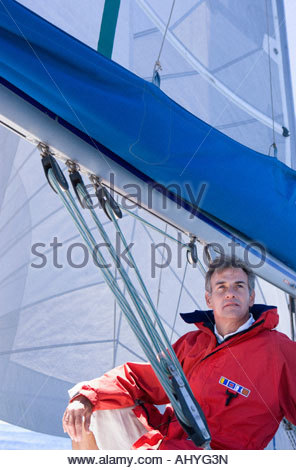 Man in red jacket sitting on deck of sailing boat below sail, smiling, low angle view - Stock Photo