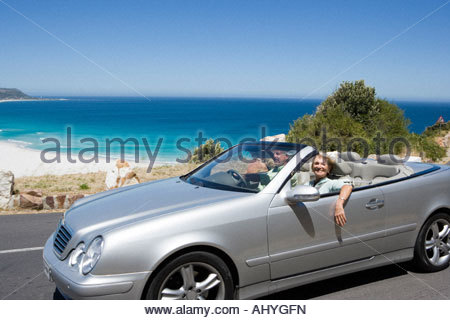 South Africa, Western Cape, senior couple driving in convertible car along coastal road, smiling, side view, portrait - Stock Photo