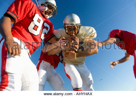 American football players tackling opposing player with ball, low angle view - Stock Photo