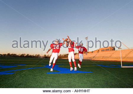 Three American football players, in red football strips, celebrating touchdown on pitch during competitive game - Stock Photo