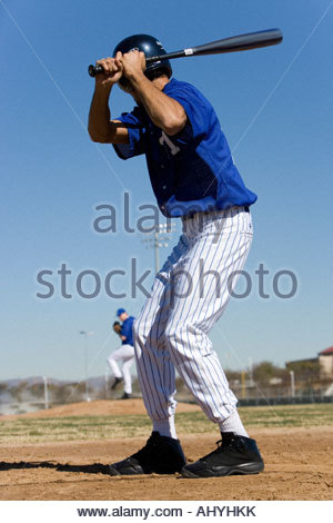 Baseball batter facing pitcher during competitive game, focus on foreground, rear view - Stock Photo