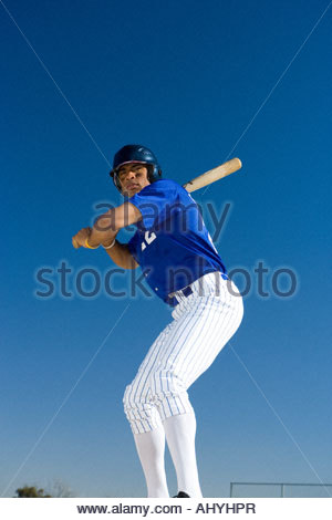 Baseball batter standing against clear blue sky, preparing to hit ball, front view, low angle view - Stock Photo