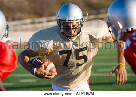 Determined American football player running with ball at opposing players during competitive game, front view tilt - Stock Photo