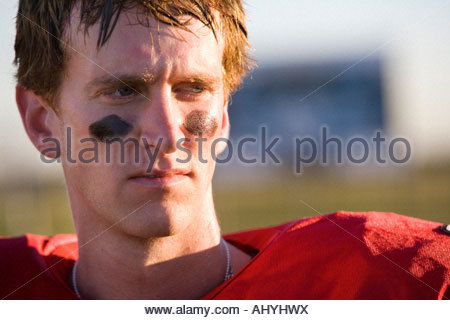 American football player wearing red football strip and black face paint, close-up, front view - Stock Photo