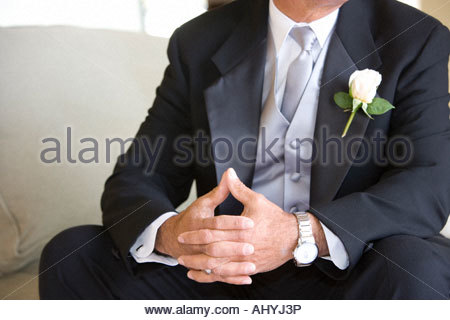 Senior groom, in formalwear, sitting on chair at wedding, thumbs pressed together, mid-section - Stock Photo