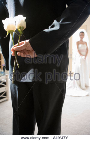 Groom holding two white roses behind back, bride standing in background, focus on groom in foreground, rear view - Stock Photo