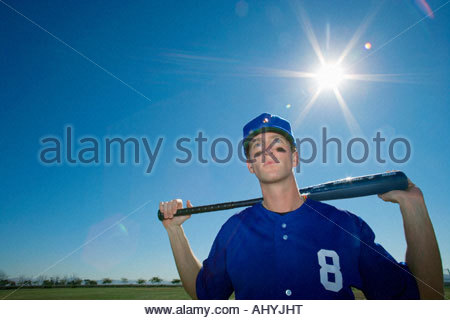Baseball player, in blue uniform and cap, standing on pitch with bat behind head, front view, portrait lens flare - Stock Photo